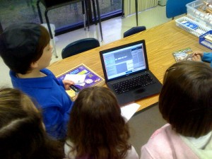 Children recording a podcast on a laptop